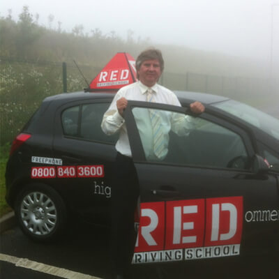 Anthony Fuller with Red Driving school car