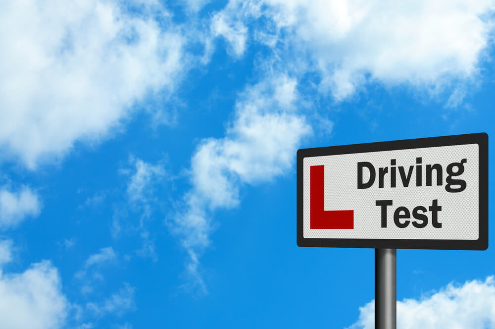 Driving test sign against blue sky
