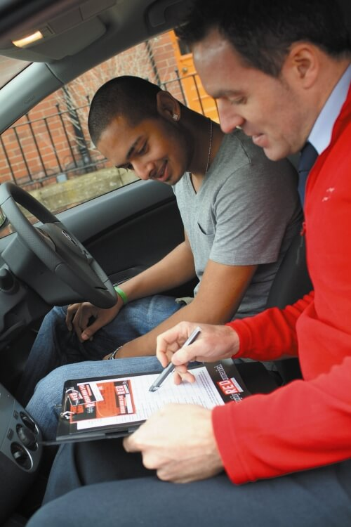 Learner with Red Driving school instructor in car