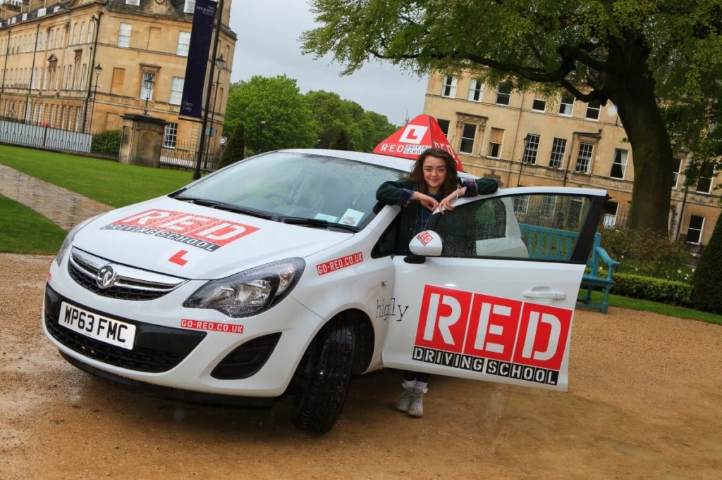 Maisie Williams outside with RED driving school car
