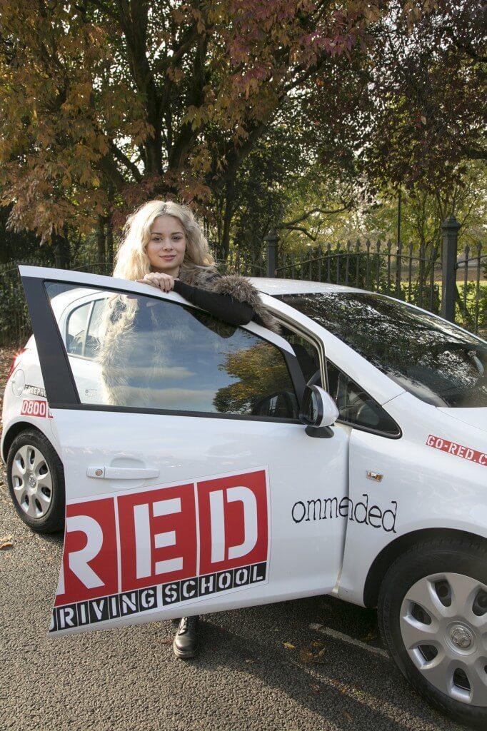 Nina Nesbitt leaning on RED driving school door