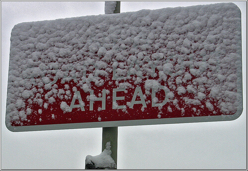 Red road sign covered with snow