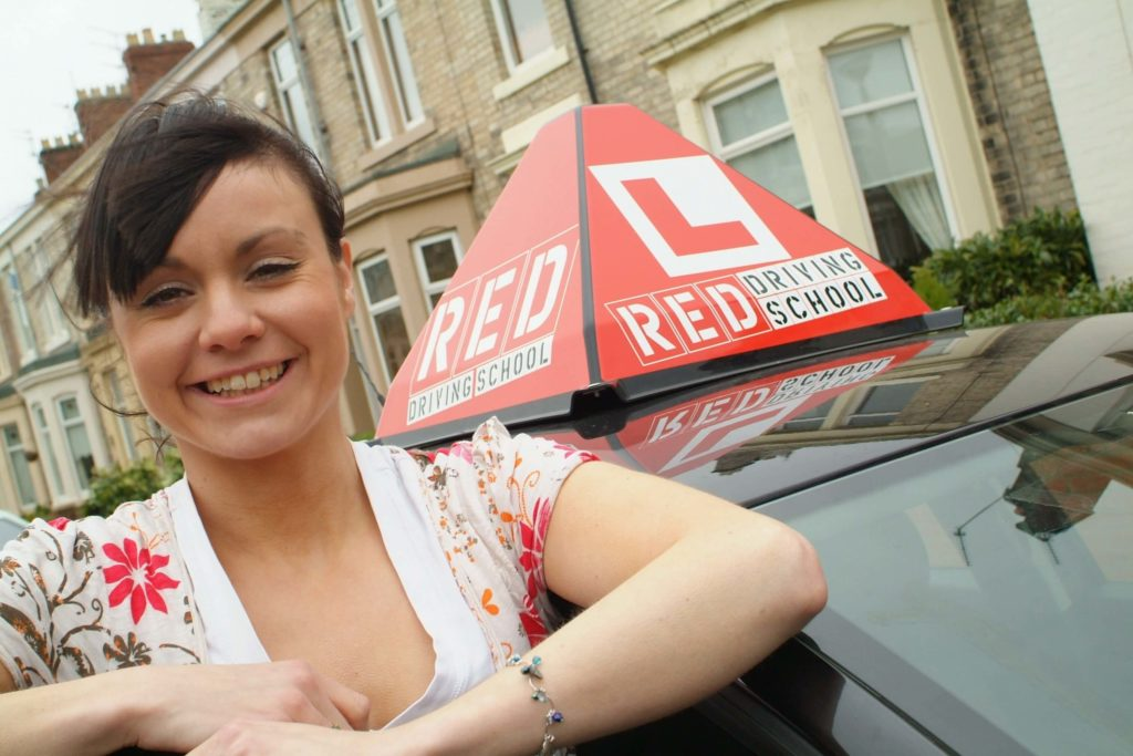 woman and red driving school car sign