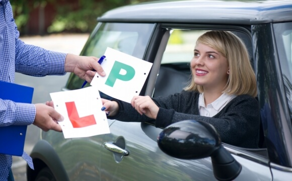 Woman swapping L Plate for P Plate
